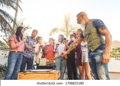 Happy family drinking red wine in barbecue party - Chef senior man grilling meat and having fun with parents - Weekend food bbq and reunion young and older people lifestyle concept