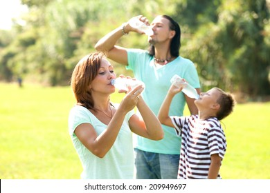 Happy family drinking water from plastic bottles in summer park