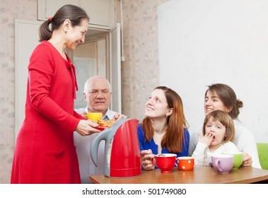 happy   family drinks tea and eats cakes