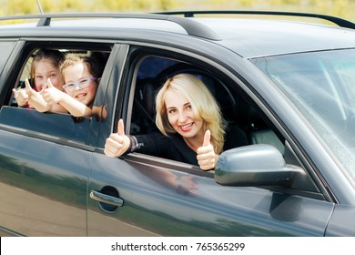 Happy family driving a car. A smiling mother drives a car. The children are watching from the rear window of the car.