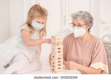 Fröhliche Familie während der Isolierung von Coronavirus. Coronavirus (Covid-19)-Epidemie. Großmutter mit Schutzmaske spielt mit ihrer kleinen Enkelin