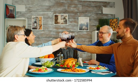 Happy family during lunch toasting with red wine. Friends and family at sunday dinner