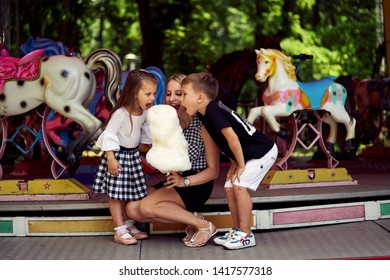Happy family eating cotton candy at an amusement park. Mother, son and daughter biting candyfloss.