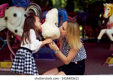 Happy family eating cotton candy at an amusement park. Mother and daughter biting candyfloss.