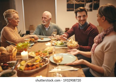 Happy family eating dinner at dining table. Focus is on young man serving food to his wife.
