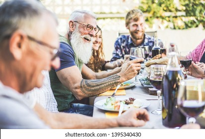 Happy family eating and drinking wine at barbecue dinner on patio outdoor - Mature and young people having fun at bbq sunday meal - Food and summer lifestyle concept - Focus on hipster man arm hand