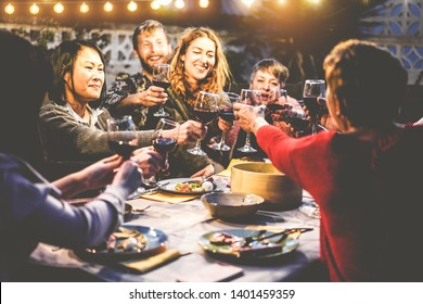 Happy family eating and drinking wine at barbecue dinner outdoor - Multiracial mature and young people having fun at bbq sunday meal - Food and summer lifestyle concept - Focus on asian woman face