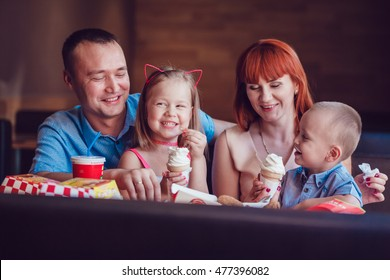 Happy family eating ice cream in restaurant