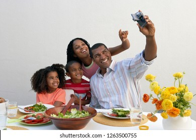 Happy family eating lunch meal at home taking selfie