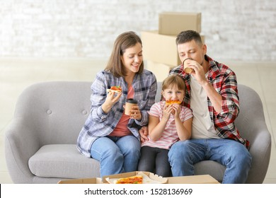 Happy family eating pizza on moving day