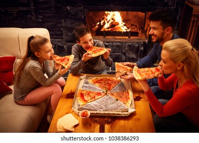Happy family eating pizza slices for the dinner together