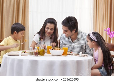 Happy family eating pizza together at restaurant