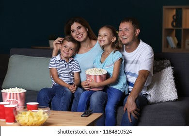 Happy family eating popcorn while watching TV in evening