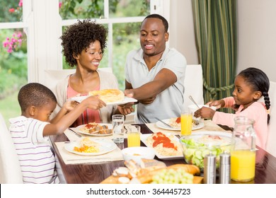 Happy family eating together at home