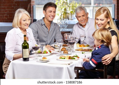 Happy family eating together in a restaurant with child and grandparents
