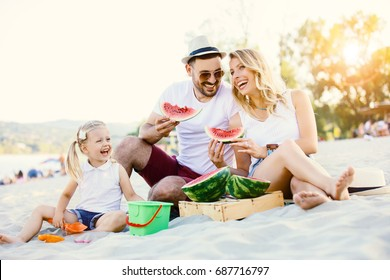 Happy family is enjoying beach and eating watermelon.