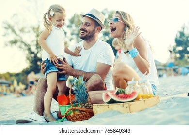 Happy family is enjoying beach and eating fruit.