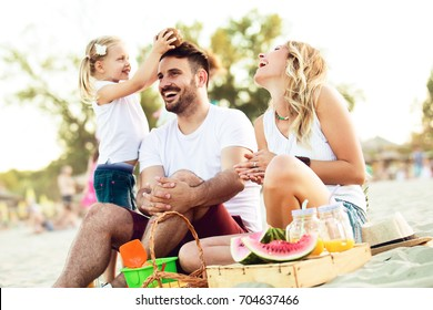 Happy family is enjoying beach and having pic-nic.
