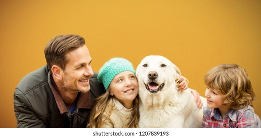 Happy family enjoying with dog in leaves against orange background