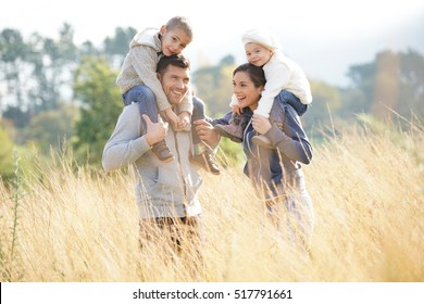 Happy family enjoying fall day in the countryside