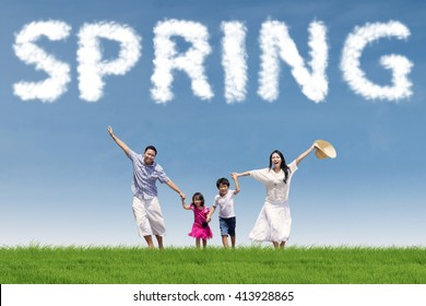 Happy family enjoying leisure time together at the field under a spring cloud