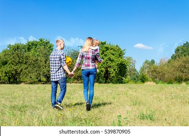 Happy family enjoying life together walking through the meadow