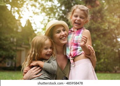 Happy family enjoying ,mother hugging hers daughters.