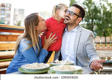 Happy family is enjoying pasta in restaurant.