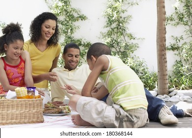 Happy family enjoying a picnic at home.