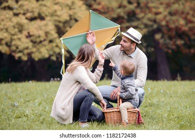 Happy family enjoying picnic in nature,they let kite and spend time together.