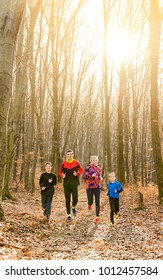 Happy family enjoying and running together in the forest at late afternoon.