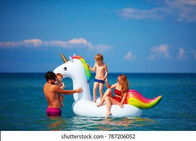happy family enjoying summer vacation, having fun in water on inflatable unicorn