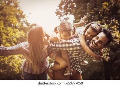 Happy family enjoying together in summer day. father carrying little girls on piggyback.