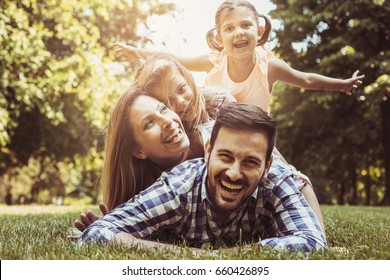 Happy family enjoying together in summer day. Little girls lying on parents piggyback.