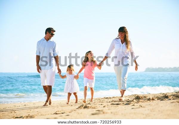 Fröhliche Familie, die am Strand spazieren geht