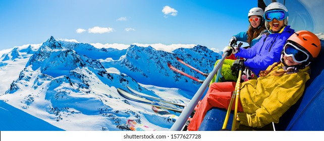 Happy family enjoying winter vacations on ski lift  in mountains, Val Thorens, 3 Valleys, France. Playing with snow and sun in high mountains. Winter holidays.