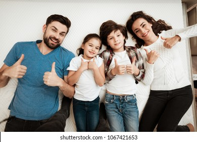 Happy family enjoys comfort of lying on a mattress inside a furniture store. The best choice of orthopedic mattress. Big family together check softness of mattress.