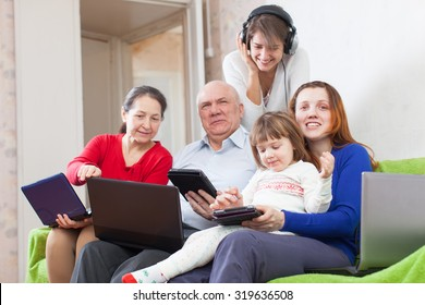 Happy family enjoys on sofa in livingroom room with few various laptops at home