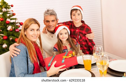 Happy family exchanging gifts for Christmas.