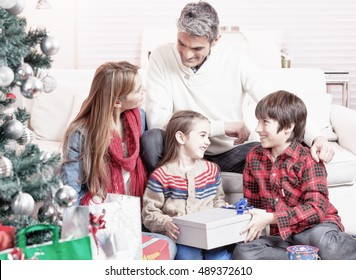 Happy family exchanging gifts under Christmas tree. Family and holiday concept. Parents and children.