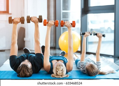 Happy family exercising with dumbbells at fitness studio