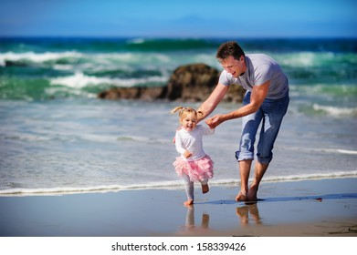 happy family father and baby girl daughter have a fun on a paradise beach ocean background