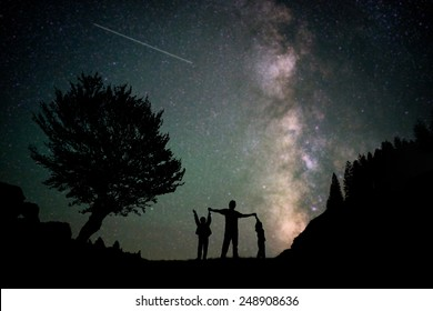 Happy family father and boys silhouette with Milky Way and beautiful night sky full of stars in background
