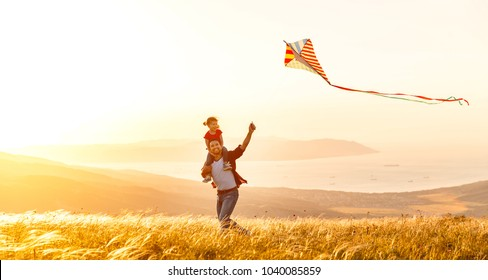 happy family father and child daughter run with a kite on meadow
