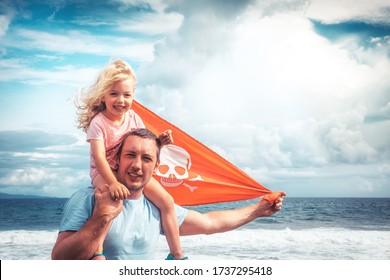 Joyeux père de famille et petite fille sur les épaules contre le ciel bleu et la mer