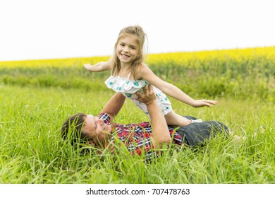 Happy family father and child daughter on yellow flowers on nature in summer