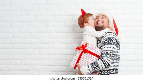 Happy family father and child with a gift in a Christmas kiss from a blank brick wall