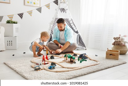 happy family father and child son playing together in toy railway in playroom
