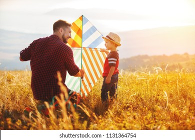 happy family father and child son launch a kite on meadow