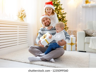 happy family father and children  playing and laughing near Christmas tree
